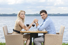 Side view portrait of young couple holding hands at outdoor restaurant by lake Royalty Free Stock Photography