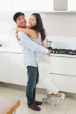 Side view portrait of a young couple in kitchen Stock Photography