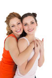 Side view portrait of a young female embracing her friend Stock Photo