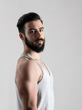 Side view portrait of young fit athlete in tank top. Looking at camera Royalty Free Stock Photos