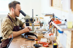 Appraiser in Pawn Shop. Side view portrait of young jeweler inspecting precious stones using microscope sitting at workshop table royalty free stock images