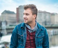 Side view portrait of young man in front of city. Sideways of gorgeous guy, outdoors Royalty Free Stock Images