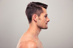 Side view portrait of a young man with nude torso. Over gray background Royalty Free Stock Images