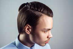 Side view portrait of young man with top knot hairstyle. Royalty Free Stock Photo