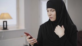 Side view portrait of young muslim woman scrolling on smartphone and gesturing no by shaking head. Modern eastern lady