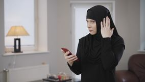 Side view portrait of young muslim woman scrolling on smartphone and touching head with hand. Thoughtful eastern lady in