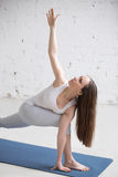 Side view portrait of young woman doing Twisting Side Angle Pose Stock Images