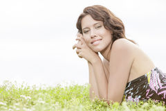Side view portrait of young woman lying on grass against clear sky Stock Image