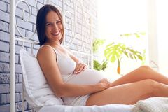 Positive future mother posing at camera on bed Stock Photo