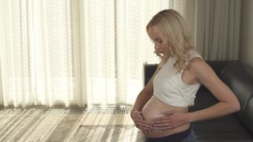 A side view of a pregnant blonde standing in the room and rubbing cream into belly. She looks at the belly and applies