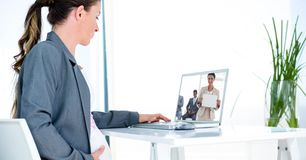 Side view of pregnant businesswoman video conferencing in office stock photography
