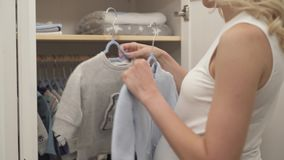 A side view of pregnant woman's hands holding a rack with a buttoned sweater for a baby. stock footage