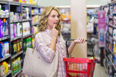 Side view of a pretty blonde woman having a shopping bag and looking at shelf Royalty Free Stock Image