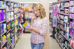 Side view of a pretty blonde woman looking at a product Royalty Free Stock Photos
