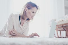 Side view of pretty blonde woman watching clothes using wi fi in royalty free stock photography
