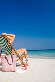 Side view of pretty brunette relaxing on deck chair at the beach Royalty Free Stock Images