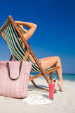 Side view of pretty brunette relaxing on deck chair at the beach Stock Photos