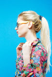 Side View of Pretty Girl with Ponytail Wearing Colorful Shirt and Eyeglasses on Blue Background in Studio. Side View of Blonde Girl with Ponytail Wearing Royalty Free Stock Photo