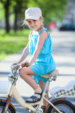 Side view of pretty girl riding on bicycle Royalty Free Stock Photos