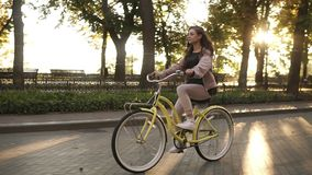 Side view pretty longhaired girl riding a bike on the street or boulevard in summer city park. Wearing pink coloured stock footage