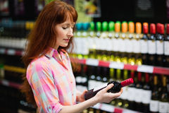 Side view of pretty woman choosing carefully a bottle of wine Royalty Free Stock Images