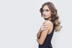 Side view of pretty woman with long brown hair. Side view of woman with long wavy brown hair who is wearing long black dress and touching her shoulder. Mock up Stock Photos