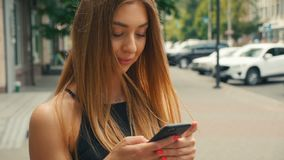 Pretty young woman typing on mobile phone with people walking in street at background, Brown haired woman looking at. Side view of pretty young woman typing on stock video footage