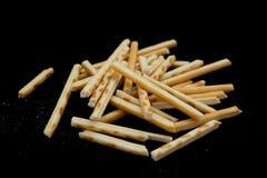 Side view pretzel sticks on black background Royalty Free Stock Photos
