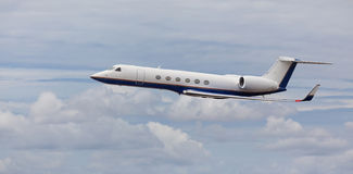 Side view of a private jet flying. With cloudy skies Stock Images