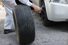 Side view of professional automotive mechanic man in uniform holding tire for fixing car at the garage background. Auto repair ser Royalty Free Stock Photo