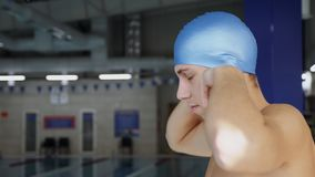 Swimmer wearing swimming cap. Side view a professional swimmer puts on a cap at an indoor pool - closeup slow motion shot stock video footage
