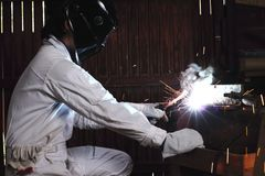 Side view of professional welder in white uniform with protective helmet welding steel with spark in workshop. Industrial worker c. Oncept Stock Images