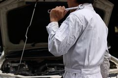 Side view of professional young mechanic man in uniform holding wrench against car in open hood at the repair garage. Side view of professional young mechanic stock photography