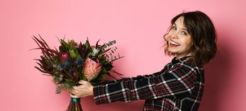 Side view profile of attractive young woman in a dark checkered dresst holding bouquet of flowers and giving you. royalty free stock photo