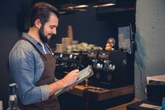 Happy worker writing information in confectionary shop. Side view profile smiling bearded barista making notes while standing in modern cafe. Job concept. Copy Stock Photo