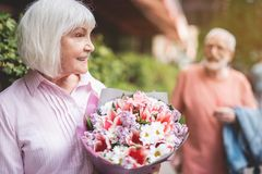 Delighted woman with bouquet outside. Side view profile of smiling senior lady standing on street with bunch of flowers in hands.  She is satisfied after saying Stock Image