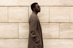 Free Side View Profile Stylish African Man Model Wearing Brown Knitted Cardigan, Sunglasses On City Street Over Brick Wall Stock Photo - 168732980