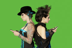 Side view of punk females standing back to back over with mobile phones over green background Royalty Free Stock Photo