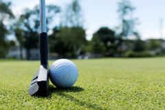 Side view of a putter and a white golf ball Royalty Free Stock Image