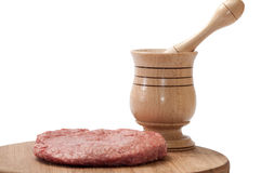 Side view of raw pljeskavica with wooden mortar on wooden board Stock Photo