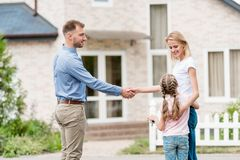 side view of realtor shaking hand of young woman royalty free stock image
