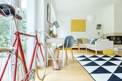 Side view of red bicycle. And designer chair at desk in white living room with yellow decoration royalty free stock photos