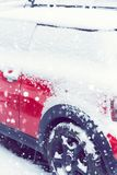 Side view of a red car covered after snowfall. Toned. Side view of a red car covered after a recent snowfall. Toned Royalty Free Stock Images