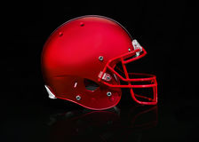 Side view of a red football helmet on a black background. A Red American football helmet on a black background Royalty Free Stock Photos
