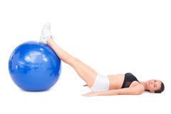 Side view of relaxed fit woman lying working out with exercise ball Stock Photo