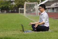 Side view of relaxed young Asian business man with laptop doing yoga position on the green grass of stadium. stock image