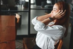 Side view of relaxed young Asian woman listening music with headphones in living room stock photo