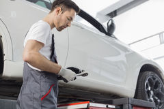 Side view of repairman holding tool while standing by car in workshop Stock Images