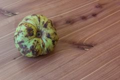 Side view of a ripe green cherimoya fruit on a wood table. Copy space, horizontal aspect Royalty Free Stock Photo