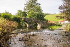 Side view of the river and historic bridge at Malmsmead in autumn. Side view of the river and historic 17th century bridge and ancient ford at Malmsmead on  the Stock Image